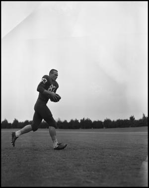 Primary view of object titled '[Football Player No. 83 Running with a Ball, September 1962]'.