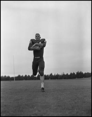 Primary view of object titled '[Football Player No. 44 Running with a Football, September 1962]'.