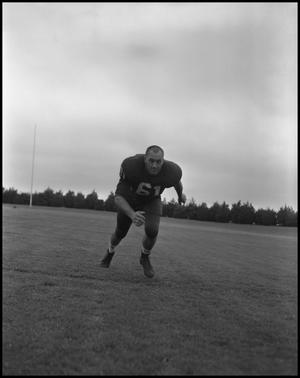 Primary view of object titled '[Football Player No. 61 Running Low on the Field, September 1962]'.