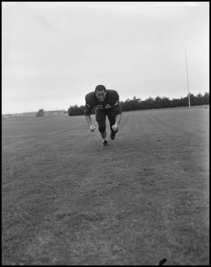 Primary view of object titled '[Football Player No. 64 Running Low on the Field, September 1962]'.