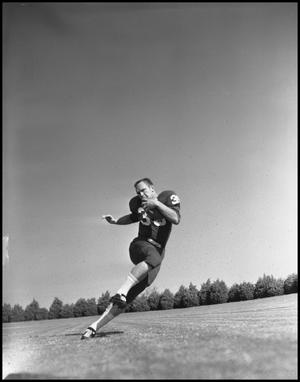 Primary view of object titled '[Football Player Running at an Angle with a Football, 1961-1962]'.