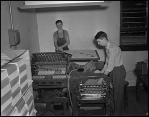 Primary view of object titled '[Two Young Men at the Printing Press]'.