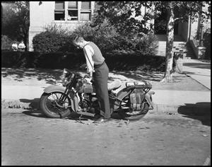 Primary view of object titled '[Student with Motorcycle in Front of Building]'.