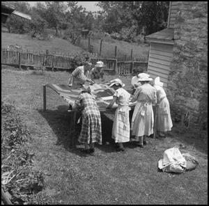 Primary view of object titled '[Women at an outdoor quilting bee]'.