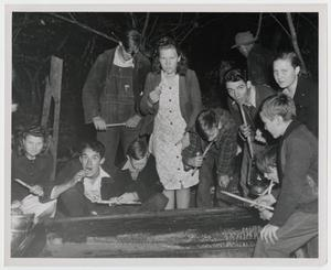 Primary view of object titled '[Kids and Adults using Sop Sticks tasting the Molasses]'.