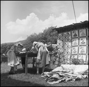 Primary view of object titled '[Women sewing at an outdoor quilting bee]'.