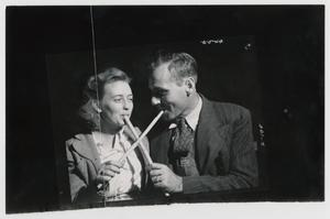 Primary view of object titled '[Couple Sampling Molasses with Sop Sticks]'.