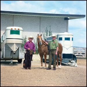 Primary view of object titled '[Rex Cauble in front of horse trailers (full view)]'.