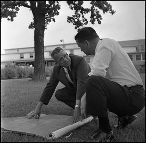 Primary view of object titled '[Dr. Farmer and Dr. Spurlock Reviewing Building Plans for the New Student Union]'.