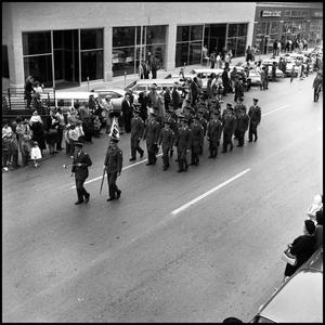 Primary view of object titled '[AFROTC members march in the Homcoming Parade November 5, 1966]'.