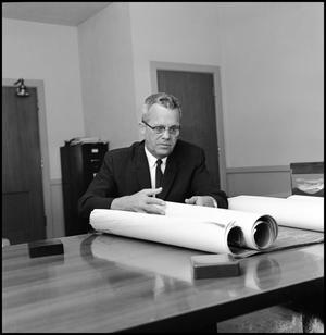 Primary view of object titled '[Dr. Wayne Adams with Blueprint]'.