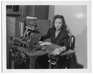 Primary view of object titled '[Woman Adjusts Mailroom Machinery]'.