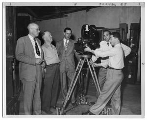 Primary view of object titled '[Five Men Standing Around a Camera]'.