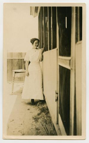 Primary view of object titled '[Woman Standing Next to a House]'.