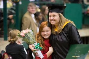 Primary view of object titled '[Graduate poses with family at UNT Commencement]'.