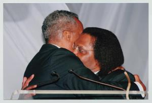 Primary view of object titled '[Curtis King Hugging Guest]'.