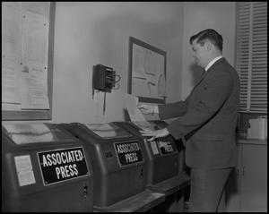 Primary view of object titled '[WBAP-TV Employee Reading from Teleprinter]'.