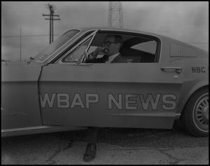 Primary view of object titled '[Bruce Neal in the WBAP News Car]'.