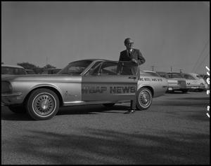 Primary view of object titled '[Bruce Neal poses in the WBAP-TV News Car]'.
