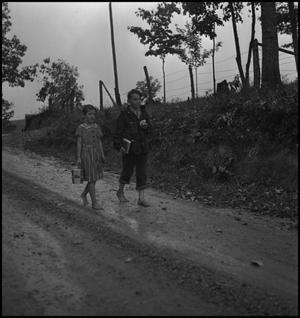 Primary view of object titled '[Children walking in the rain(1)]'.