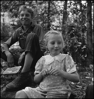 Primary view of object titled '[Otto Walker and girl eating lunch outside]'.