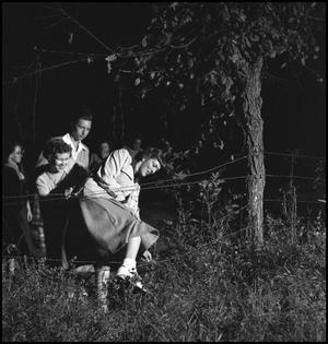 Primary view of object titled '[Young woman climbing through fence]'.