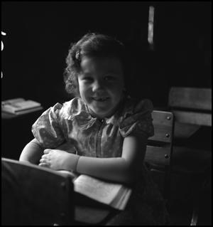 Primary view of object titled '[Smiling student at her desk]'.
