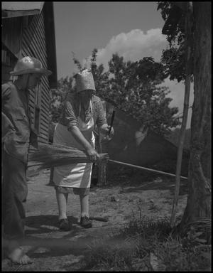 Primary view of object titled '[Aunt Nora Treece watering the broom]'.