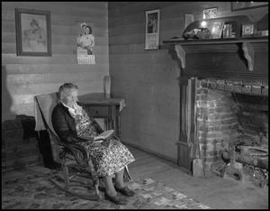 Primary view of object titled '[Aunt Julia McCreary sitting by a fireplace]'.
