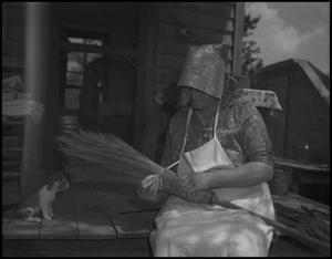 Primary view of object titled '[Aunt Nora Treece flattening the new broom]'.