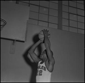 Primary view of [Oscar Miller jumping with a basketball]