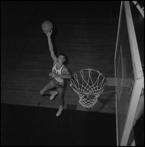 Primary view of object titled '[Aerial view of Zack Hayes jumping with a basketball]'.