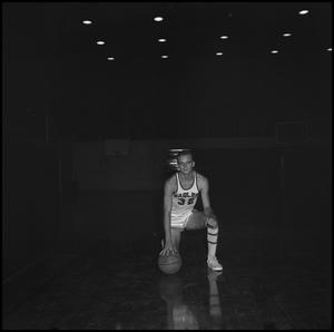 Primary view of object titled '[Johnny Burks kneeling with a basketball, 2]'.