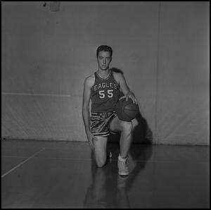 Primary view of object titled '[Butch Pruett kneeling in the gym]'.