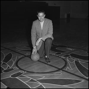 Primary view of object titled '[Head Coach Charles Johnson kneeling with a basketball]'.