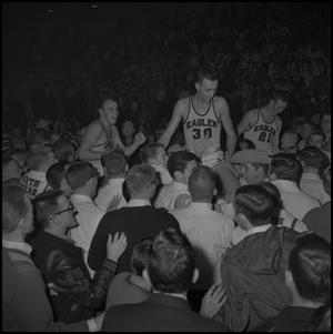 Primary view of object titled '[Three NTSU basketball players lifted by the crowd]'.