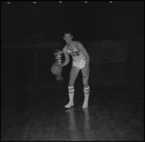 Primary view of object titled '[Carl Miller dribbling a basketball]'.