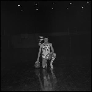 Primary view of object titled '[John Jones kneeling with basketball, 2]'.