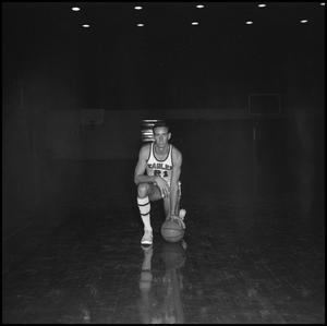 Primary view of object titled '[Doug Reedy kneeling with basketball]'.