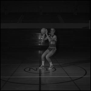 Primary view of [Basketball player holding ball at eye level]