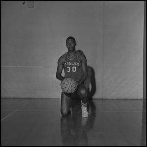 Primary view of object titled '[Alan Canselo kneeling with his basketball]'.