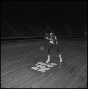 Primary view of object titled '[Carl Jones dribbling a basketball]'.