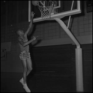 Primary view of object titled '[Basketball player tossing up ball into hoop]'.