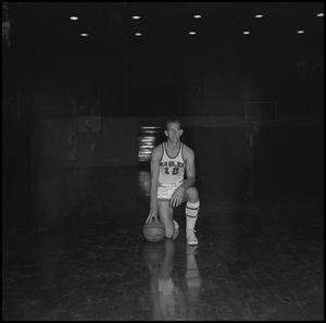 Primary view of object titled '[Carroll Carlisle kneeling with basketball]'.