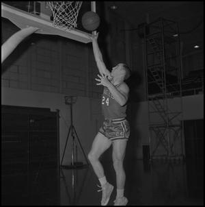 Primary view of object titled '[Ron Miller going to dunk basketball]'.