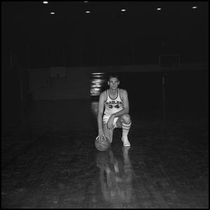 Primary view of object titled '[Carl Miller kneeling with his basketball]'.