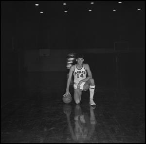 Primary view of object titled '[John Jones kneeling with basketball]'.