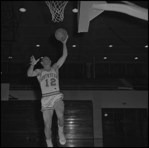 Primary view of object titled '[Ron Miller jumping up with basketball in hand, 2]'.