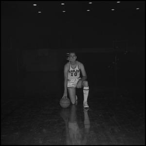Primary view of object titled '[Billy Hughes kneeling with his basketball, 2]'.