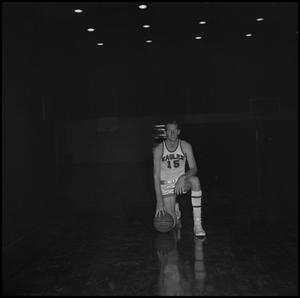 Primary view of object titled '[Eddie Davis kneeling with a basketball]'.